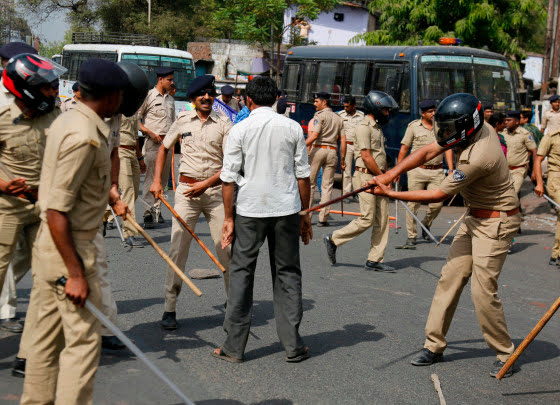 Image: Indian policemen beat a lower caste Dalit protestor during a nationwide strike in Ahmadabad, India.